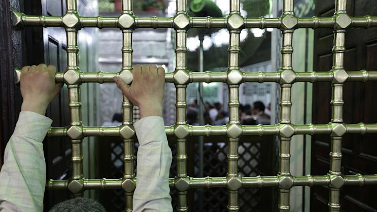 In this Thursday, June 6, 2013 photo, a man is praying as he holds the iron cage that contains the tomb of at the shrine of Imam Hussein, the grandson of Islam's prophet Muhammad and one of the most believed Shiite saints, in Cairo, Egypt. Egypt's roughly 15 million Sufi Muslims say their places of worship are under threat by rising radicalism. They say that since the country's 2011 uprising that toppled longtime autocrat Hosni Mubarak, shrines held sacred to them have been attacked by hardliners who deem them heretical and idolatrous. (AP Photo/Hassan Ammar)