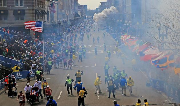 People react as an explosion goes off near the finish line of the 2013 Boston Marathon in Boston, Monday, April 15, 2013. Two explosions went off at the Boston Marathon finish line on Monday, sending