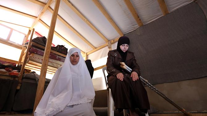 Syrian refugees women, who fled their home from Syria, pray inside their tent at a Syrian refugee camp in the eastern town of Marj in Bekaa valley, Lebanon, Sunday, June 29, 2014. Across a wide belt that stretches halfway around the globe, the world's estimated 1.6 billion Muslims mark the beginning of Ramadan this weekend. The holy season is marred by unprecedented turmoil, violence and sectarian hatreds that threaten to rip apart the Middle East, the epicenter of Islam. (AP Photo/Bilal Hussein)