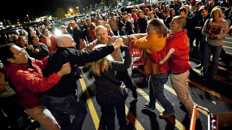 A crowd gathers as security guards break up a fight between shoppers waiting in line just as the doors open for Black Friday shopping at Target, Thursday, Nov. 22, 2012, in Bowling Green, Ky. Stores typically open in the wee hours of the morning on the day after Thanksgiving that's called Black Friday because of retail folklore that it's when merchants turn a profit for the year. After testing how shoppers would respond to earlier hours last year, stores such as Target and Toys R Us this year opened as early as Thanksgiving evening. That created two separate waves of shoppers. (AP Photo/Daily News, Alex Slitz)