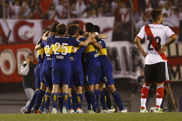 Boca Juniors players, left, celebrate after defeating River Plate in an Argentina's league soccer match in Buenos Aires, Argentina, Sunday, Oct. 6, 2013