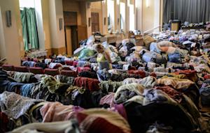A woman checks clothes piled up in a room of a building…
