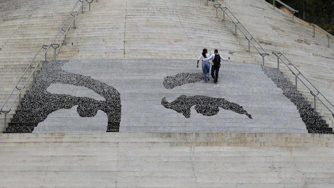 A couple climbs a flight of stairs with tiles depicting the eyes of late Venezuelan President Hugo Chavez, in Caracas