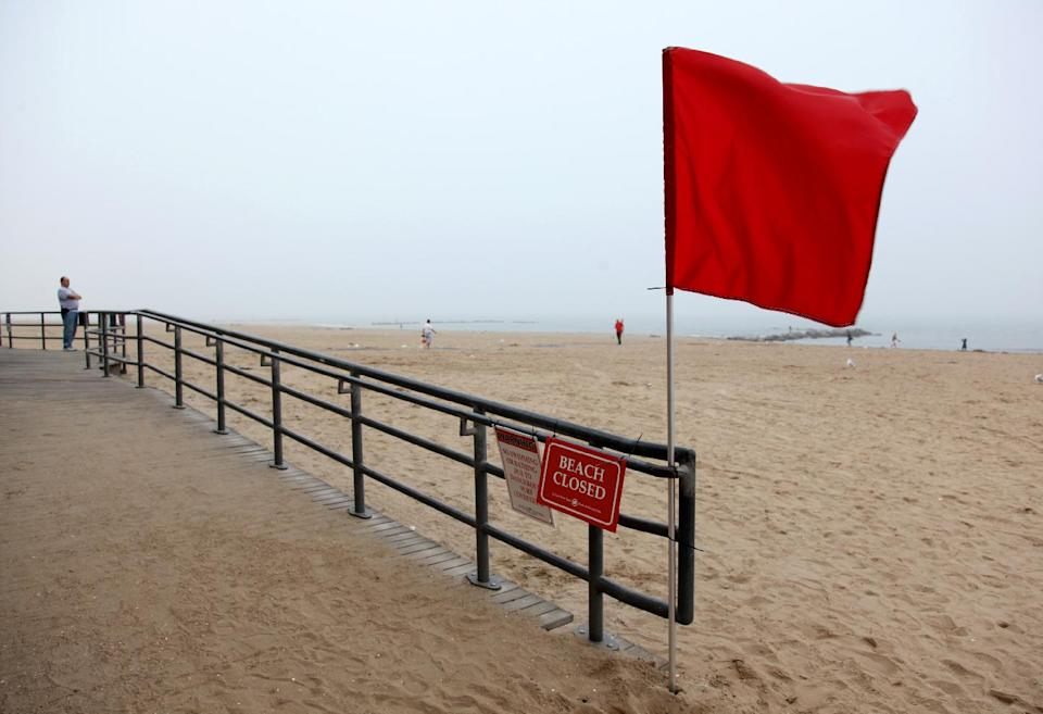 Thomas Walker, of Merrick, N.Y., far left, who runs a business on the Coney Island boardwalk, looks out over the adjacent closed beach as he and others await the arrival of Hurricane Irene, Saturday, Aug. 27 2011, in the Coney Island section of  New York. (AP Photo/Craig Ruttle)