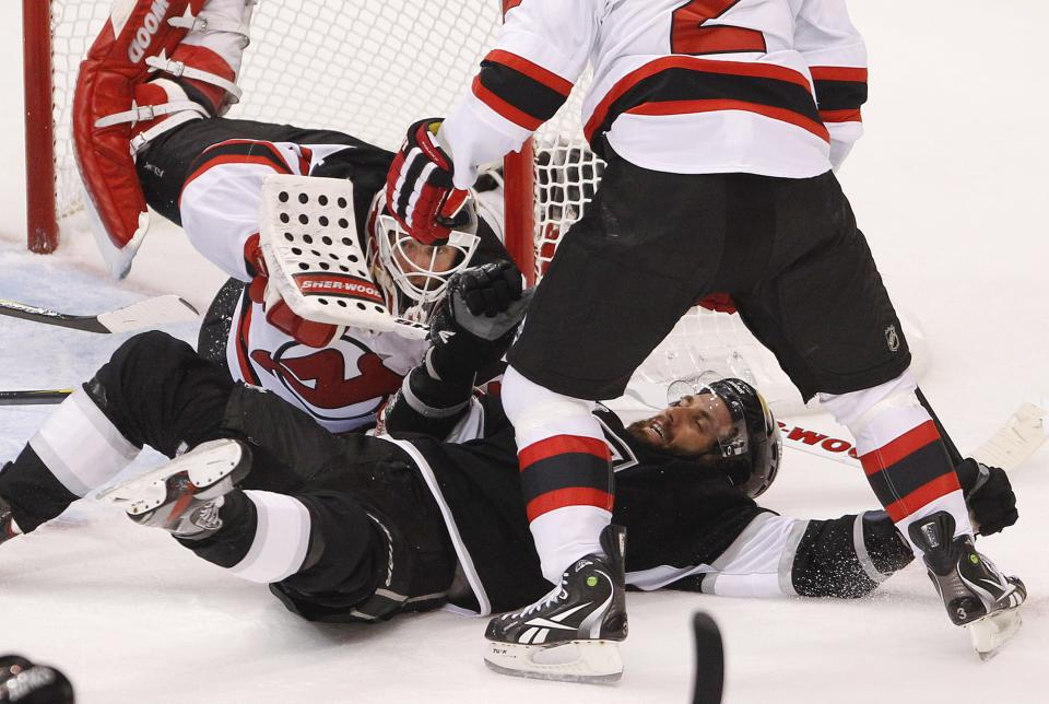 Los Angeles Kings center Jarret Stoll (28) falls to the ice as New Jersey Devils goalie Martin Brodeur, left, defends in the second period during Game 4 of the NHL hockey Stanley Cup finals, Wednesday, June 6, 2012, in Los Angeles.  (AP Photo/Jae C. Hong)
