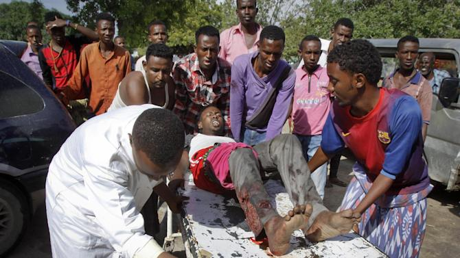 Somalis push a wounded civilian on a stretcher into a hospital following clashes between Somali troops and militiamen loyal to a Somali warlord in Mogadishu, Somalia Friday, Aug. 15, 2014. The sounds of warfare rattled Mogadishu residents from their beds early Friday as government troops launched a dawn attack on a house belonging to a former warlord as part of a disarmament campaign. (AP Photo/Farah Abdi Warsameh)