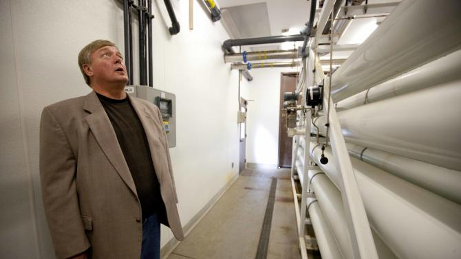 In this photo taken Thursday, Sept. 13, 2012,  Jim Heitzman, general manager of the Marina Coast Water District, looks over the interior of a shut down desalination plant in Marina, Calif.  Not long ago, the idea of squeezing salt from the ocean to make clean drinking water was embraced warmly in thirsty California with its cycles of drought and growing population. But it has not panned out the way many hoped. Desalination plants are costing more to build; they're huge energy suckers and lingering concerns about the impact to marine life have spurred myriad lawsuits. (AP Photo/Eric Risberg)