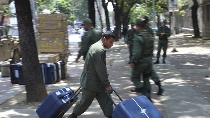A soldier unloads cases containing voting machines at a polling station in Caracas, Venezuela, Wednesday, April 10, 2013. Venezuela's presidential election is scheduled for Sunday, April 14. (AP Photo/Ramon Espinosa)