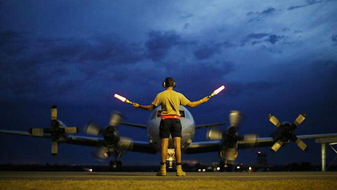 FILE - In this Monday, March 24, 2014, file photo, a ground controller guides a Royal Australian Air Force AP-3C Orion to rest after sunset upon its return from a search for the missing Malaysia Airlines Flight 370, over the Indian Ocean, at the Royal Australian Air Force Base Pearce in Perth, Australia. The disappearance of Malaysia Airlines Flight 370 has presented two tales of modern technology. The public has been surprised to learn of the limitations of tracking and communications devices, which contributed to the plane vanishing for more than two weeks. But the advanced capabilities of some technologies, particularly satellites, have provided hope that the mystery won't go unsolved. (AP Photo/Jason Reed, Pool, File)