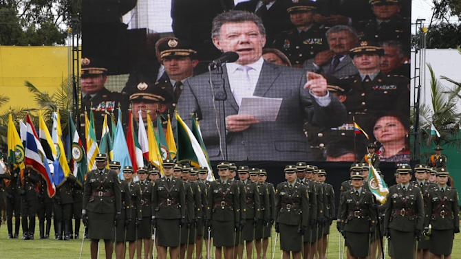 "Colombia's President Juan Manuel Santos' live image covers a screen behind female police attending their promotion ceremony in Bogota, Colombia, Friday, June 21, 2013. Santos said he regrets the death of Special Agent James ""Terry"" Watson, who was assigned to the DEA office in Cartagena. Watson died in an apparent robbery attempt in Colombia, U.S. Ambassador to Colombia Michael McKinley said Friday. Colombian authorities said the American agent was stabbed four times in Bogota. (AP Photo/Fernando Vergara)"