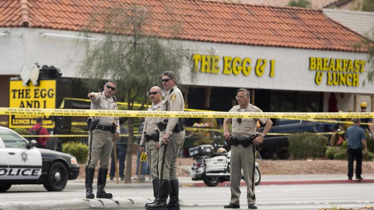 Las Vegas Metro police officers examine the scene of an accident where a vehicle crashed into a crowded restaurant, Monday, April 1, 2013, in Las Vegas. Ten people were seriously injured and at least one person was arrested Monday after the car plowed into the patio of the Egg & I restaurant during the lunch hour and came to rest with its hood inside a shattered plate glass window. Victims were transported to two nearby hospitals with non-life threatening injuries after the crash shortly after 12:30 p.m. (AP Photo/Julie Jacobson)