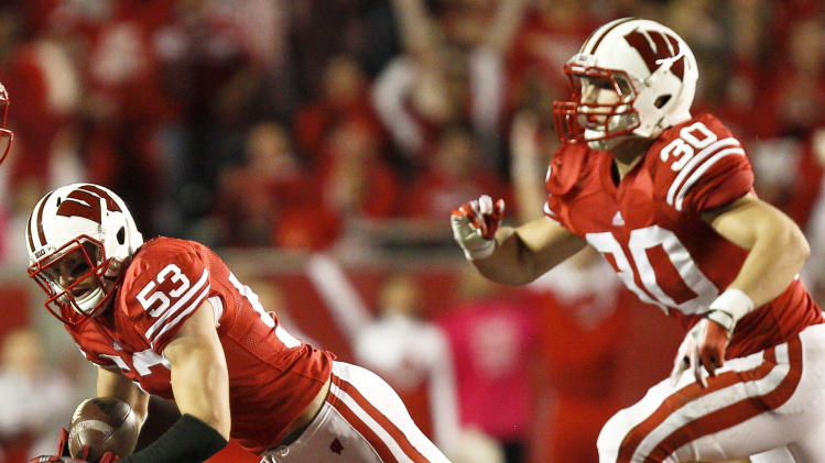 Wisconsin linebacker Mike Taylor (53) is tackled by Rex Burkhead (22) after Taylor's interception during the first half of an NCAA college football game, Saturday, Oct. 1, 2011, in Madison, Wis. (AP Photo/Andy Manis)