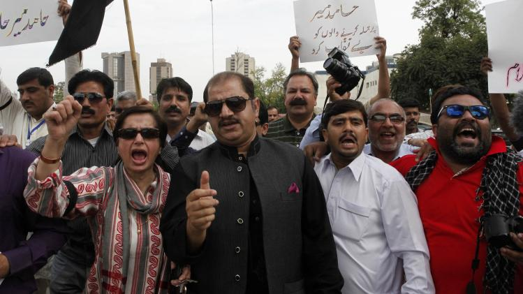 Pakistani journalists chant slogans during a protest, called by PFUJ, against the attack on television anchorperson Hamid Mir, outside the press club in Karachi