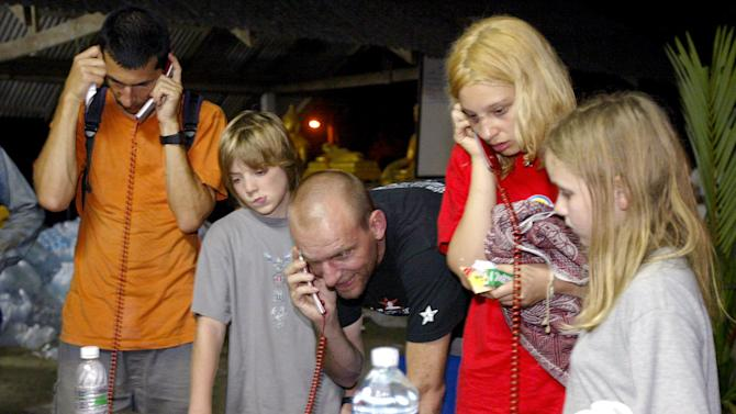 A day after the disaster, stranded tourists use phones provided for free at a Buddhist temple in Khao Lak, Thailand, so they can make international calls to give news to relatives and friends abroad
