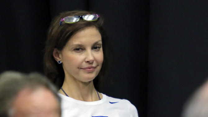 Actress Ashley Judd watches the Kentucky news conference after Kentucky's 68-66 win over Notre Dame in a college basketball game in the NCAA men's tournament regional finals, Saturday, March 28, 2015, in Cleveland. (AP Photo/Aaron Josefczyk)