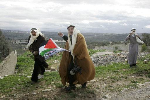 Traditionally dressed Palestinian men hurl stones at Israeli security forces during a protest in the village of Kufr Qaddum near the Israeli settlement of Kdumim, in the northern West Bank, Friday, Jan. 13,  2012. (AP Photo/Nasser Ishtayeh)