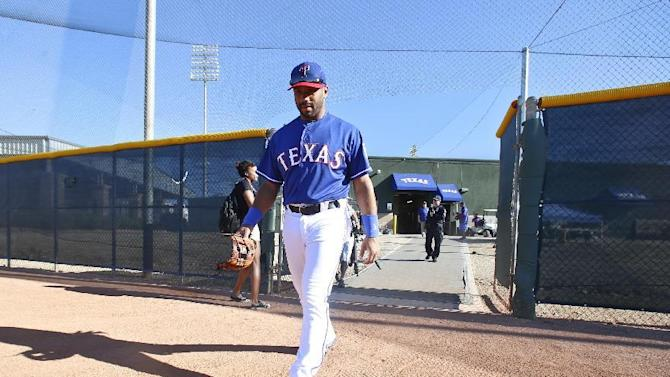 Seattle Seahawks quarterback Russell Wilson walks onto the practice field for  early infield practice prior to a Rangers spring training baseball game against the San Diego Padres, Saturday, March 28, 2015, in Surprise, Ariz.  (AP Photo/Lenny Ignelzi)