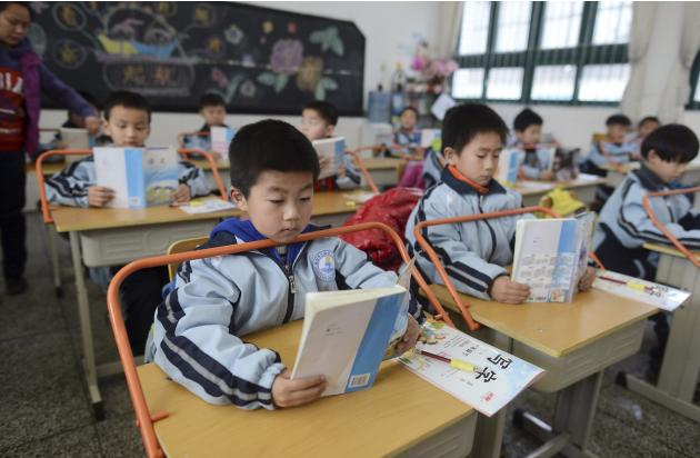 Pupils read books as they sit on refitted desks aiming to prevent student nearsightedness, at a primary school in Wuhan
