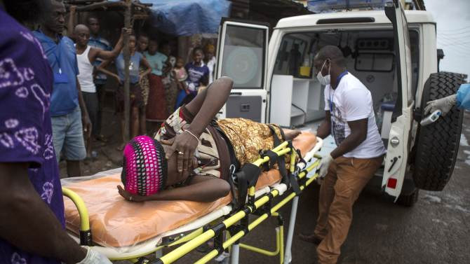 A pregnant woman suspected of contracting Ebola is lifted by stretcher into an ambulance in Freetown