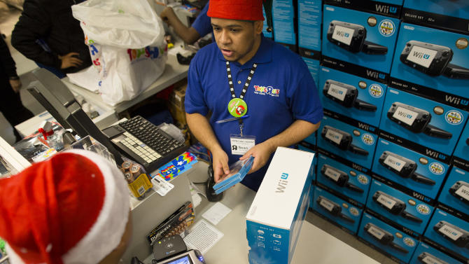 FILE - In this Thursday, Nov. 22, 2012, file photo, a customer makes a purchase in the Times Square Toys-R-Us store in New York. U.S. retail sales rose 0.3 percent in November from October, the Commerce Department said Thursday. That offset a 0.3 percent decline in October from September. (AP Photo/John Minchillo, File)