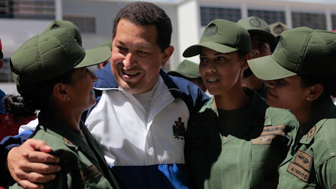 In this photo provided by Miraflores Presidential Press Office, Venezuela's President Hugo Chavez, center, shares a moment with female Army cadets during a visit to Alejandro Petion military academy at Fuerte Tiuna in Caracas, Venezuela, Thursday, July 7, 2011. Ailing Chavez appeared live on television Thursday, meeting with cadets and other soldiers at the country's largest military base and vowing to survive his recent surgery to remove a cancerous tumor.(AP Photo//Miraflores Presidential Press Office)