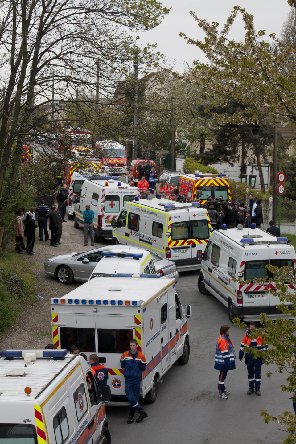 Emergency workers are seen around the area of a building accident, in Pierrefitte, north of Paris, Sunday April 8, 2012. French officials say a floor has collapsed at a building where an Easter religious ceremony was being held, killing a 6-year-old and seriously injuring four other people. (AP Photo/Thibault Camus)