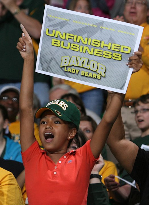 Elizabeth Green, 9, watches large video monitors in Waco, Texas, as Baylor takes on Notre Dame in the NCAA women's college basketball tournament Final Four championship game in Denver, Tuesday, April