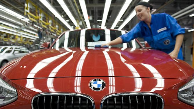 The July 7, 2011 photo shows a BMW employee cleans the hood of a BMW in the BMW plant in Regensburg, southern Germany.  Strong sales of its luxury cars in China helped Germany's BMW AG overcome weak markets in crisis-ridden Europe. BMW announced Tuesday, Nov. 6, 2012 net profit rose 16 percent in the third quarter to euro 1.29 billion (US$1.65 billion) on a 13.7 percent jump in sales to a record euro 18.82 billion. (AP Photo/dapd, Lennart Preiss)