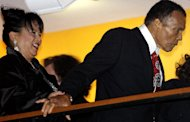 Boxing great Muhammad Ali, right, with the help of his sister-in-law, Marilyn Williams, left, makes an appearance at a balcony before the celebration for his 70th birthday at the Muhammad Ali Center on Saturday, Jan. 14, 2012, in Louisville, Ky. Ali turns 70 Tuesday. (AP Photo/Mark Humphrey)