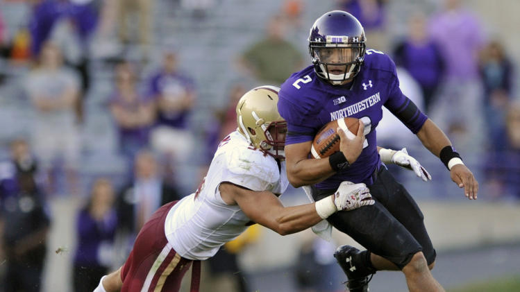 Northwestern quarterback Kain Colter, right, rushes while being tackled by Boston College's Nick Clancy  during the fourth quarter of an NCAA college football game on Saturday, Sept. 15, 2012, in Evanston, Ill. Northwestern won 22-13. (AP Photo/Paul Beaty)