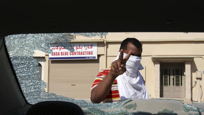 A Bahraini man gestures from behind a car in Barbar, Bahrain, on Friday, Nov. 9, 2012, that residents said was damaged when it was hit by tear gas canisters fired by riot police. Police used tear gas in several villages to prevent residents from leaving to participate in midday prayers in the northern village of Diraz. Shiite clerics nationwide had called for worshipers to pray in Diraz on Friday where top Shiite cleric Sheik Issa Qassim preaches in a show of support for him at a time of concern among Shiites that he may be arrested as part of a government crackdown on the opposition. (AP Photo/Hasan Jamali)