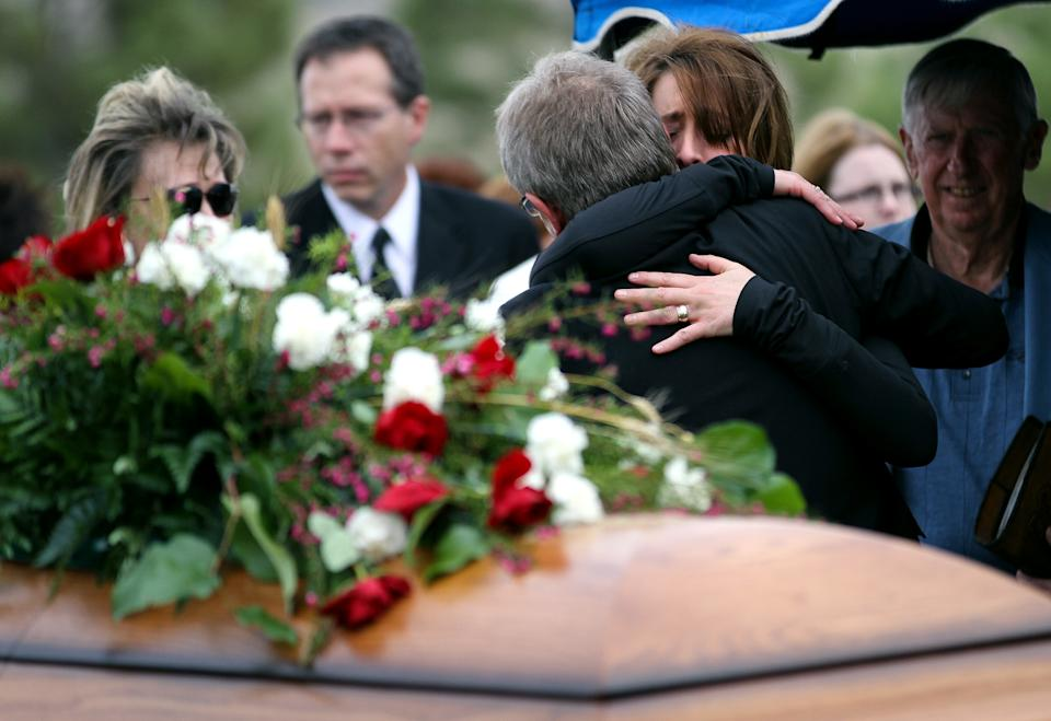 Leigh Merritt comforts Gary Arnold at the casket during Sherry Arnold's funeral service in Sidney, Mont. on Friday, March 30, 2012. Arnold was kidnapped and murdered after disappearing in January. (AP Photo/Williston Herald, Elijah Nouvelage)