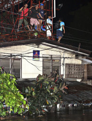 Trapped residents are perched on the roof following a flash flood that inundated Cagayan de Oro city, Philippines, Saturday, Dec. 17, 2011. A tropical storm triggered flash floods in the southern Philippines, killing scores of people and missing more. Mayor Lawrence Cruz of nearby Iligan said the coast guard and other rescuers were scouring the waters off his coastal city for survivors or bodies that may have been swept to the sea by a swollen river. (AP Photo/Erwin Mascarinas)