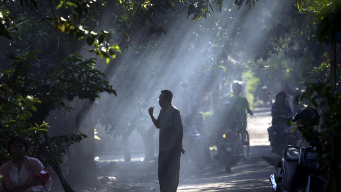 """CORRECTS PHOTOGRAPHER'S NAME - In this Monday, April 18, 2011 photo, a man is silhouetted by rays of morning sunlight at the village where Muhammad Syarif who blew himself at a mosque inside a police compound on April 15 used to live in Cirebon, West Java, Indonesia. Recent terror attacks in the world's most populous Muslim country have been carried by individuals or small groups, have been less deadly and have targeted local """"infidels"""" instead of Westerners, signaling the country's success in tamping down on its main underground terror networks, but also shows how radical groups still operating in the open remain potent breeding grounds where angry young men can turn into attackers. (AP Photo/Achmad Ibrahim)"""