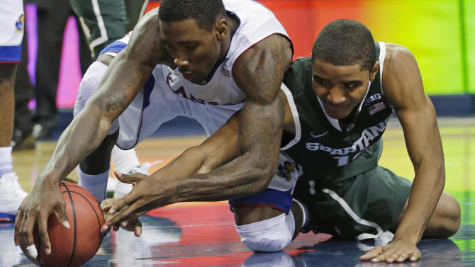 Kansas forward Jamari Traylor (31) fights for a loose ball with Michigan State guard Gary Harris (14) during the second half of an NCAA college basketball game at the Georgia Dome in Atlanta Tuesday, Nov. 13, 2012. Michigan State beat Kansas 67-64. (AP Photo/Dave Martin)