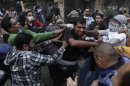 Protesters hit a riot policeman during clashes near Tahrir Square in Cairo