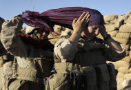 FILE - In this Aug. 10, 2009 file photo, U.S. Marine Sgt. Monica Perez, of San Diego, left, helps Lance Cpl. Mary Shloss of Hammond, Ind. put on her head scarf before heading out on a patrol with Golf Company, 2nd Batallion, 3rd Regiment of the 2nd MEB, 2nd MEF, in the village of Khwaja Jamal in the Helmand Province of Afghanistan. Perez and Shloss are members of the Female Engagement Team whose mission is to engage with local Afghan women. On Thursday, Feb. 9, 2012, Pentagon rules will catch up a bit with reality, recommending to Congress that women be formally allowed to serve in more jobs closer to the front lines. (AP Photo/Julie Jacobson, File)