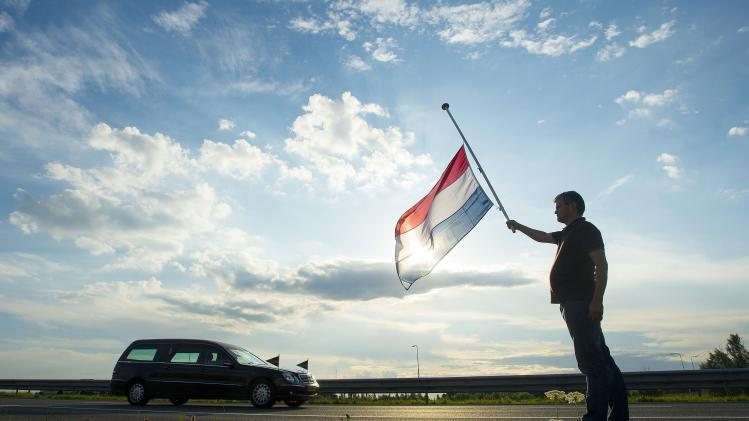 Visee holds a Netherlands flag flying at half-mast as a hearse carrying the remains of victims of flight MH17 are escorted on highway A27 near Nieuwegein