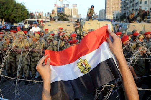 Egyptian soldiers stand guard behind barbed wire as protesters demonstrate outside the defence ministry in Cairo