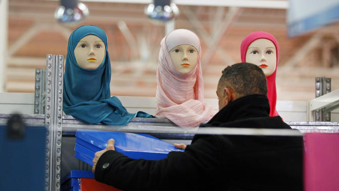 A vendor sets up his stall on the first day of the 30th Annual Meeting of  France's Muslims, at Le Bourget, Europe's largest and most popular Muslim convention, Friday March 29, 2013, on the fringes of the Parisian suburb of Le Bourget.  (AP Photo/Remy de la Mauviniere)