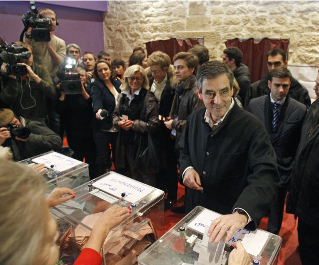Former French prime minister Francois Fillon and candidate to head the conservative UMP party, cast his vote at a polling station in Paris, Sunday Nov. 18, 2012. Frances conservative UMP party votes 