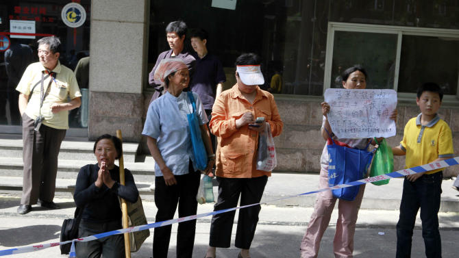Chinese petitioners protest about their own grievances near a cordon for journalists gathered outside the hospital where blind activist lawyer Chen Guangcheng is recuperating in Beijing, Saturday, May 5, 2012. While it appears China will likely make a rare concession and allow activist Chen Guangcheng to leave China with his family, dissidents say the deal is not a sign of a broader easing of controls. Authorities might even tighten the screws on other prominent critics to prevent them from seeking similar offers ahead of a leadership handover during which stability is paramount. (AP Photo/Ng Han Guan)