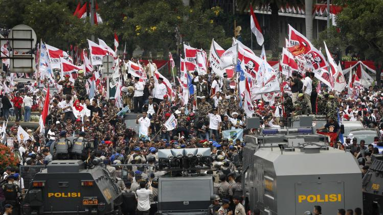 Supporters of losing presidential candidate Prabowo rally in front of police outside the Constitutional Court in Jakarta