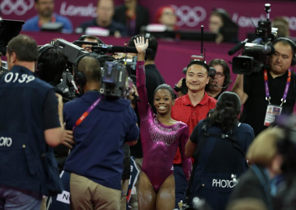 U.S. gymnast Gabrielle Douglas raises her hand after completing her final and deciding routine on the floor during the artistic gymnastics women's individual all-around competition at the 2012 Summer Olympics, Thursday, Aug. 2, 2012, in London. (AP Photo/Gregory Bull)
