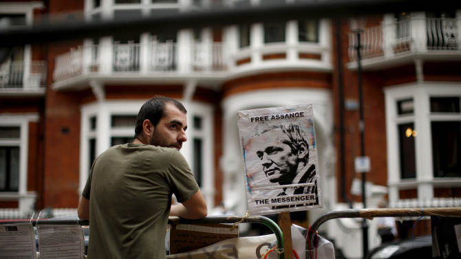 """A supporter of WikiLeaks founder Julian Assange maintains a presence outside the Ecuador embassy in London, as he continues his refuge there, Monday, Aug. 20, 2012.  Wikileaks founder Julian Assange portrayed himself Sunday as a victim of an American """"witch hunt"""" over his secret-spilling website in a defiant address from the balcony of the embassy where he is holed up to avoid extradition to face sex assault allegations.  Surrounded by British police who want to detain him, Assange made no mention of the sex assault case in Sweden or how long he would remain in Ecuador's embassy in London, where he took refuge two months ago.  (AP Photo/Matt Dunham)"""