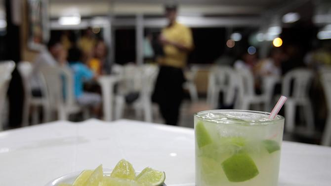 """In this April 11, 2013 photo, a glass of """"caipirinha"""" sits on a restaurant table in Brasilia, Brazil, April 11, 2013. The vast majority of cachaca, Brazil's national spirit, is consumed domestically, much of it sipped in Brazil's famed caipirinha cocktails with lime, sugar and crushed ice. (AP Photo/Eraldo Peres)"""