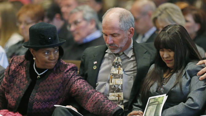 Delphia Hawkins, left, reaches over Stan Blanchard, center, to comfort Martha Martinez, right, during  a ceremony to mark the 18th anniversary of the April 19, 1995, bombing of the Oklahoma City federal building in Oklahoma City, Friday, April 19, 2013. Martinez lost her husband, Gilbert Martinez, in the blast.  Similar to previous years, 168 seconds of silence was observed at 9:02 a.m., when a truck bomb detonated outside the federal building. Survivors and family members recited the names of those killed in the attack. (AP Photo/Sue Ogrocki, Pool)