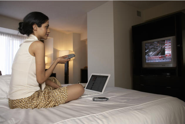 Businesswoman on hotel bed watching financial news