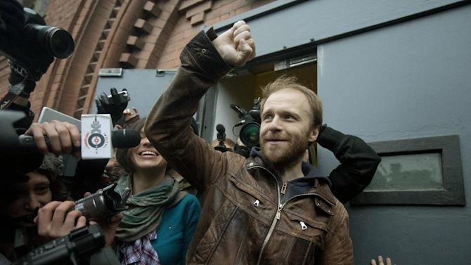 "Russian freelance photographer Denis Sinyakov, center, rises his fist outside the gates of ""Kresty"" St. Petersburg prison, after he was released in St. Petersburg, Russia, Thursday, Nov. 21, 2013. Two more of the 30 people arrested by Russia following a Greenpeace protest in the Arctic two months ago have been freed on bail. Sinyakov and activist Andrei Allakhverdov walked out of a detention center on Thursday. The 30 were arrested in September after a Greenpeace ship, the Arctic Sunrise, entered Arctic waters despite Russian warnings. (AP Photo/Pavel Golovkin)"