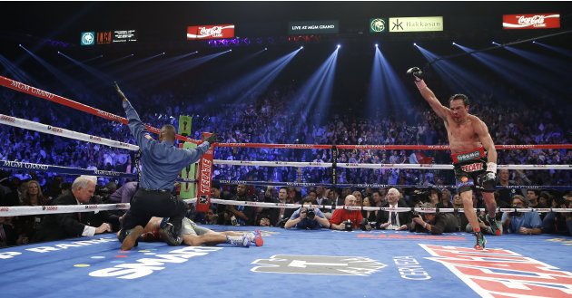 Referee Kenny Bayless, left, calls the fight as Juan Manuel Marquez, from Mexico, right, celebrates after he knocked out Manny Pacquiao, from the Philippines, lower left, in the sixth round of their W